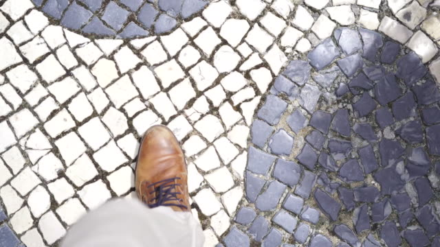 close up shot of feet walking along a stone road - walking point of view stock videos & royalty-free footage