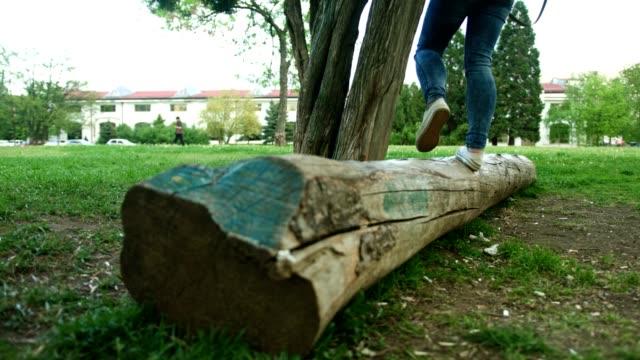 vídeos y material grabado en eventos de stock de cerrar tiro de pies mujer con zapatos de lona y jeans caminando y equilibrio sobre un tronco de árbol caído - troncos