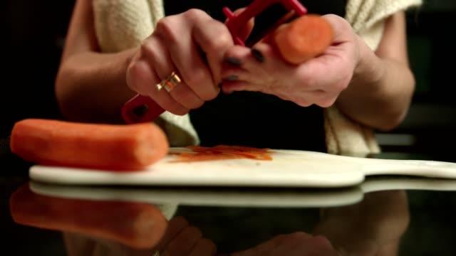 キッチン カウンターの上にニンジンを剥離女性の手のショットを閉じる - ジェンダー・ステレオタイプ点の映像素材/bロール