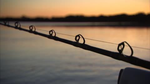 vídeos de stock, filmes e b-roll de close up shot of fishing rod at sunset - caniço