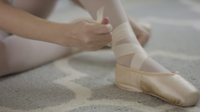 Close up shot of girl sitting on floor tying ballet shoe / Provo, Utah, United States