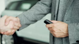 Close up shot of hands receiving car keys and shaking hands with salesman after successful deal in motor showroom. Buying and selling autos, businessmen and handshake concept.