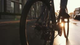 Close up shot of handsome young man driving his bicycle on the street in city center during sunrise, slow motion