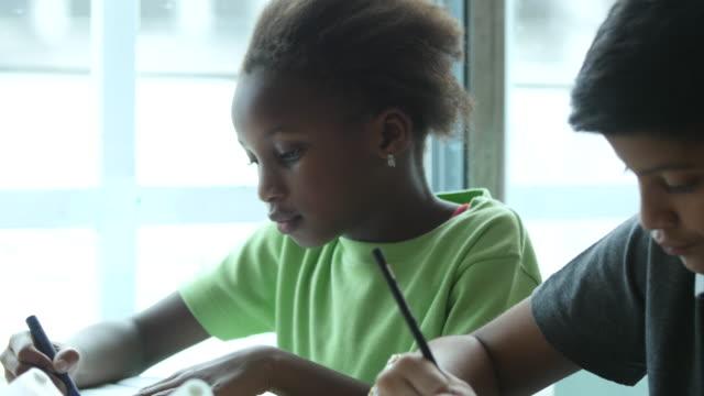 vídeos de stock, filmes e b-roll de close-up tiro de crianças em uma escola rural fazendo seu trabalho durante o tempo de aula - pobreza questão social
