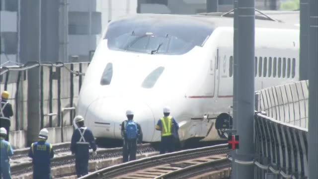 close up shot of kyushushinkansen bullet train track tilting up to a derailed bullet train carriage track workers working on derailment recovery... - kyushu shinkansen stock videos and b-roll footage