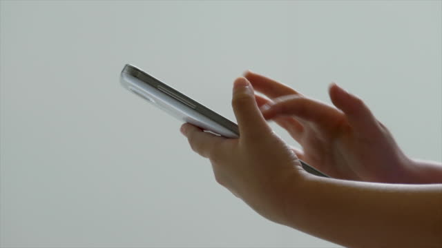 Close up shot of little girl's fingers pressing a touchscreen on the smartphone in kitchen
