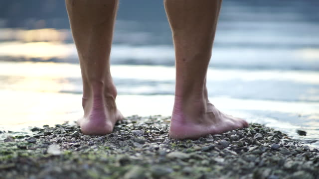 close up shot of male feet approaching a body of water - standing stock videos & royalty-free footage