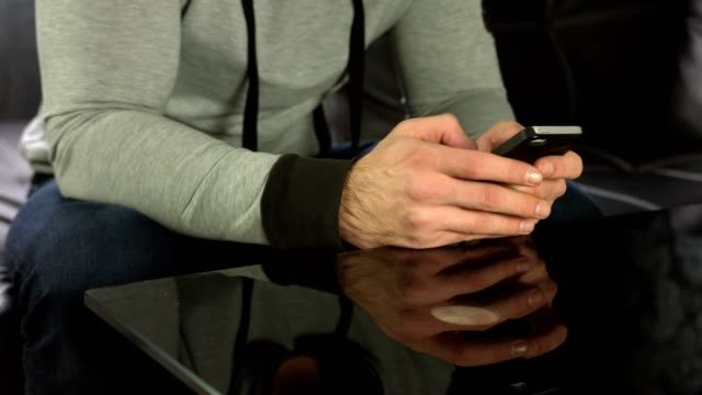 Close up shot of man's hands using a smart phone at home