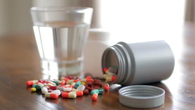 Close-up shot van geneeskunde capsule met houten tafel achtergrond met drinkwater