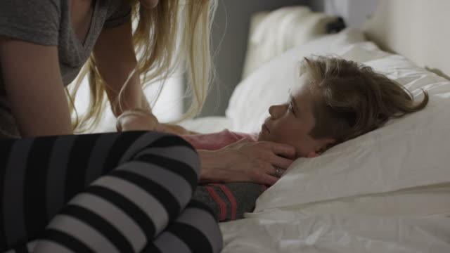 stockvideo's en b-roll-footage met close up shot of mother comforting son in bed / cedar hills, utah, united states - kussen beddengoed