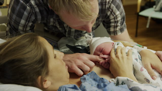 close up shot of parents admiring newborn baby in hospital / midvale, utah, united states - baby blanket stock videos and b-roll footage