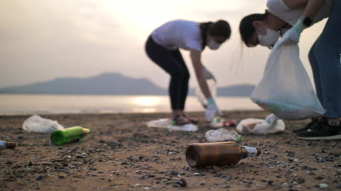 close up shot of people picking up plastic bottles on the beach, slow motion, environment conservation - picking up stock videos & royalty-free footage