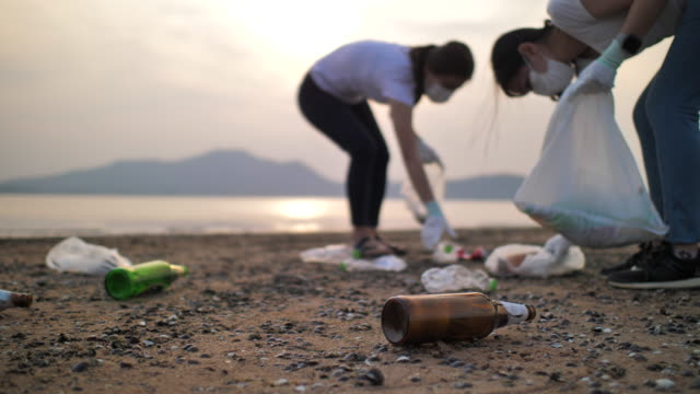 close up shot of people picking up plastic bottles on the beach, slow motion, environment conservation - garbage stock videos & royalty-free footage