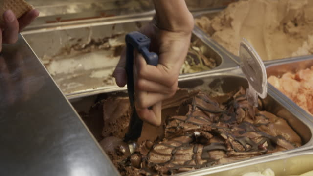 close up shot of person scooping chocolate ice cream into cone / salzburg, austria - serving scoop stock videos & royalty-free footage