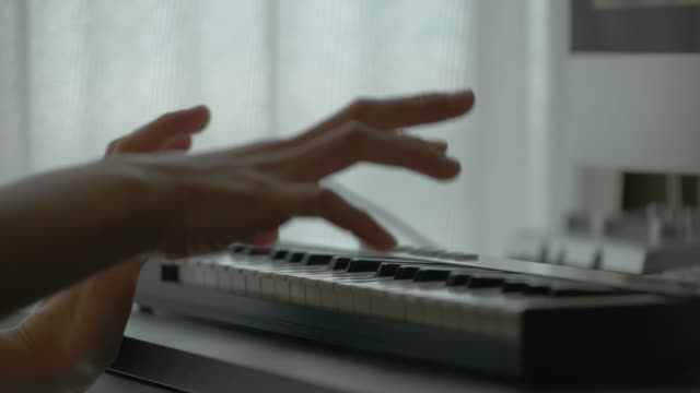 Close up shot of playing keyboard instrument.