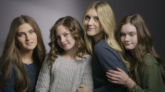 Close up shot of portrait of four sisters smiling together in studio / Cedar Hills, Utah, United States