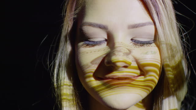 'Close up shot of projections of money on woman‰Ûªs face / Cedar Hills, Utah, United States'