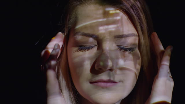 "vidéos et rushes de ""close up shot of projections on stressed woman‰ûªs face / cedar hills, utah, united states"" - image projetée"