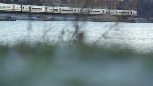 Close up shot of river with two trains appearing from opposite ends of the frame on a winter day