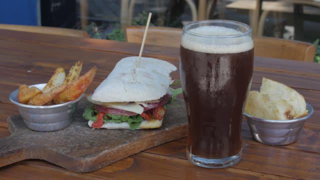 サンドイッチ、フライド ポテト、ビールのショットを閉じる - 塩味スナック点の映像素材/bロール