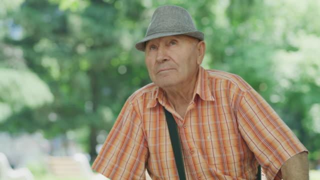 Close up shot of serious elderly man sitting in park / Kazanluk, Bulgaria