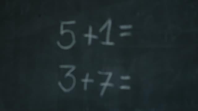 stockvideo's en b-roll-footage met sluit omhoog schot van eenvoudige vergelijkingen op zwart raad bij een basisschool - plusteken