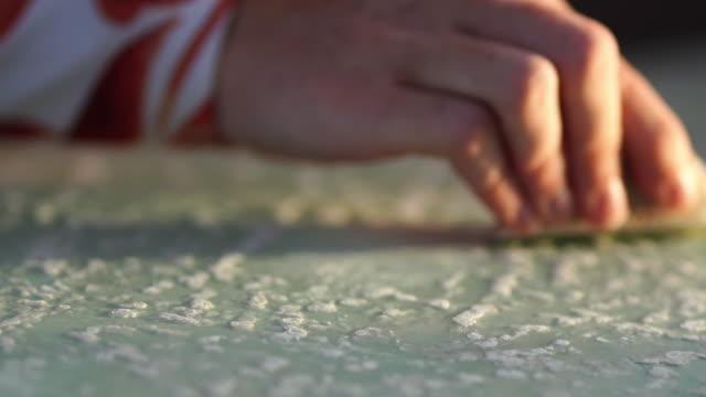 vídeos y material grabado en eventos de stock de tiro de cerca de surfista chica decerando tabla de surf en la playa - tabla de surf