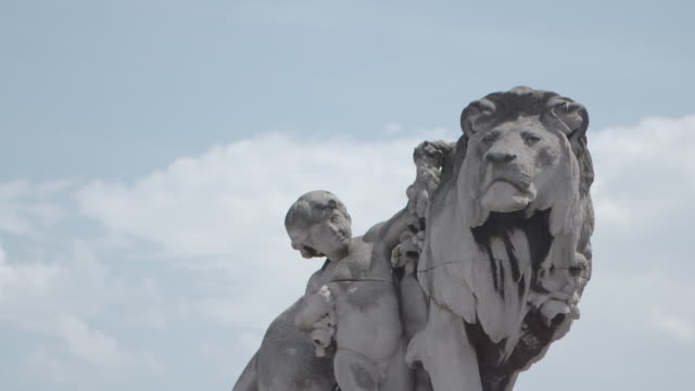 close up shot of the 'lion a l'enfant' sculpture on the pont alexandre iii bridge in paris, france - pont alexandre iii stock videos & royalty-free footage