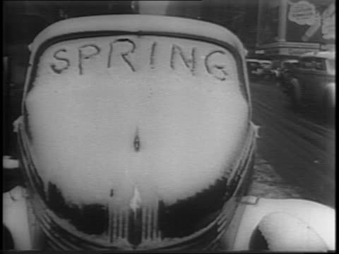 Close up shot of the word 'spring' written in snow on the windshield of a car / Shots of tips of flowers peak out of drifts of snow with profile of a...