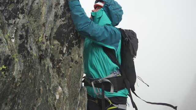 vídeos y material grabado en eventos de stock de disparo de cerca de dos excursionistas subiendo por una ladera rocosa con equipo de lluvia - riesgo