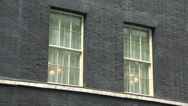close up shot of two large bay windows with lights on inside at number 10, downing street - erkerfenster stock-videos und b-roll-filmmaterial