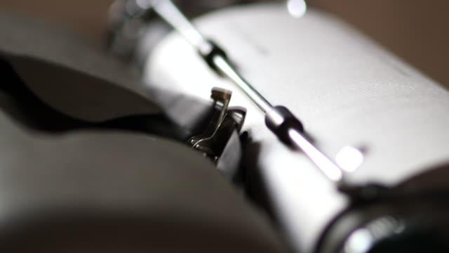 close up shot of typebars on a mechanical typewriter, striking white paper - skrivmaskin bildbanksvideor och videomaterial från bakom kulisserna