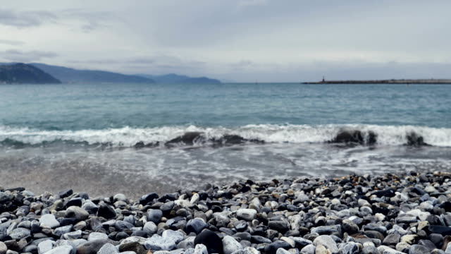Close Up Shot of Waves Rolling Up Stone Beach
