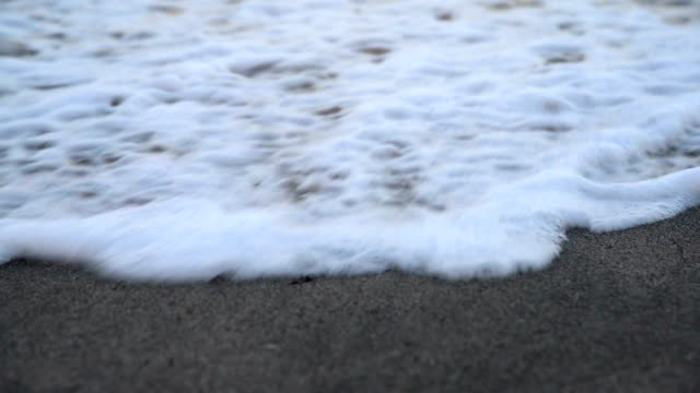 Close Up Shot of Waves Rolling Up White Sand Beach.