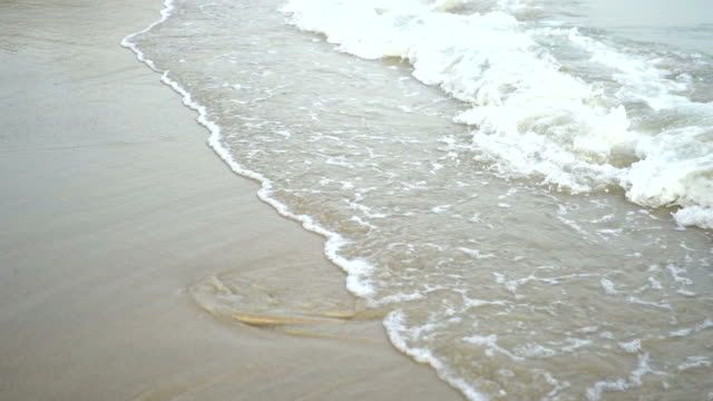 Close Up Shot of Waves Rolling Up White Sand Beach