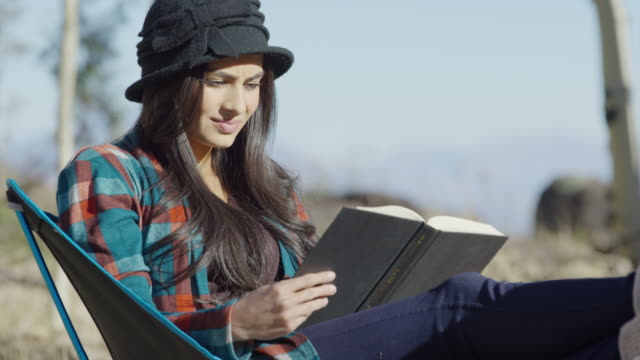 close up shot of woman camping and reading book / boulder, utah, united states - chair stock videos and b-roll footage