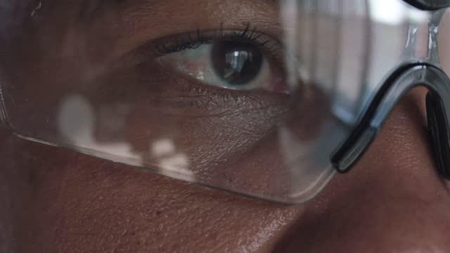 vidéos et rushes de gros plan d'une femme en lunettes de protection, détournement de regard - lunettes de protection