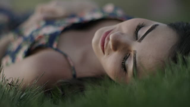 Close up shot of woman laying on back in grass / Cedar Hills, Utah, United States