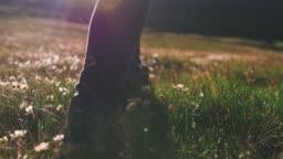 Close up shot of woman legs hiking steep terrain on field, slow motion
