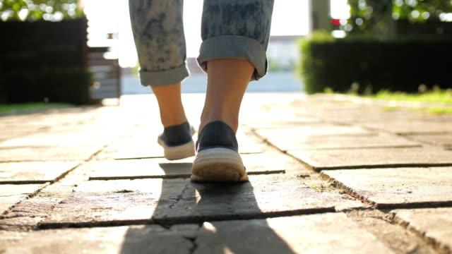 日光を浴びて歩く女性脚のクローズアップショット、スローモーション - サウンドトラック点の映像素材/bロール