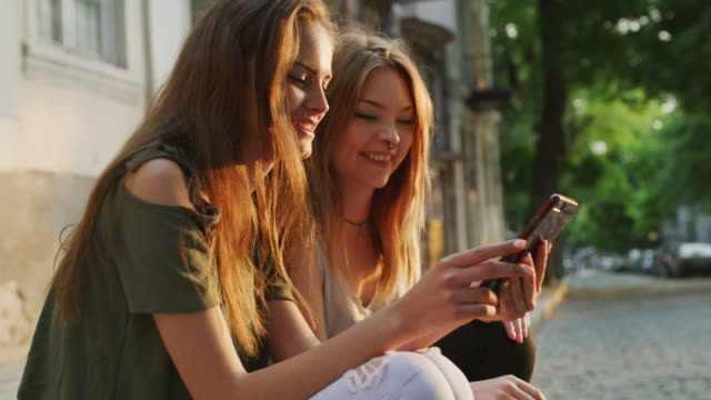 close up shot of women sitting on curb texting on cell phone / plovdiv, bulgaria - nose piercing stock videos & royalty-free footage