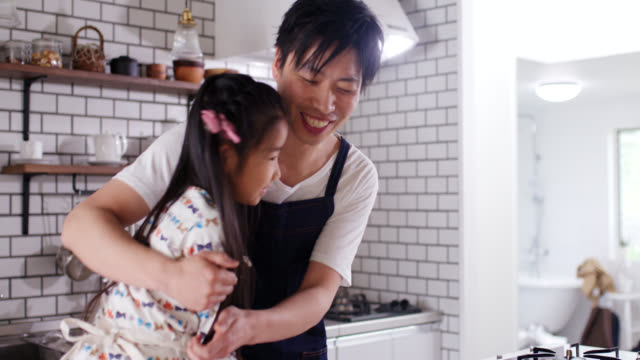 close up shot of young father talking to his daughter whilst he cooks - single father stock videos & royalty-free footage