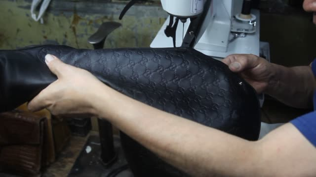 Close up shots of a shoe repair professional working on a damaged black leather female boot using a sewing machine to restitch a loose seam