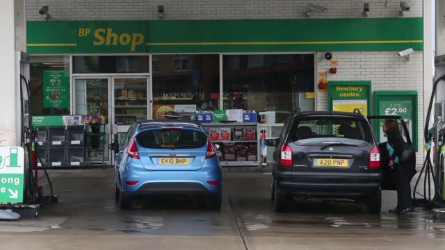 Close up shots of BP signage and gas prices at one of their refueling stations in London England UK Wide shot of two customers refueling their...