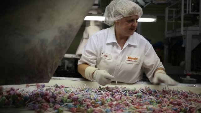 close up shots of dum dum lollipops being wrapped with wrapping paper during the manufacturing process at the spangler candy company plant in bryan,... - plant process stock videos & royalty-free footage