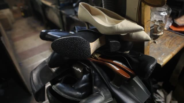 close up shots of various brands of shoes waiting to be repaired at jim's shoe repair shop on 59th street in new york ny close up shot of a chanel... - workbench stock videos & royalty-free footage