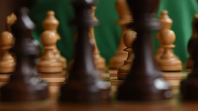 stockvideo's en b-roll-footage met close up shots pan across a chess board from behind looking through the line of black pieces at at the white pieces on the other side shot on july... - schaakstuk