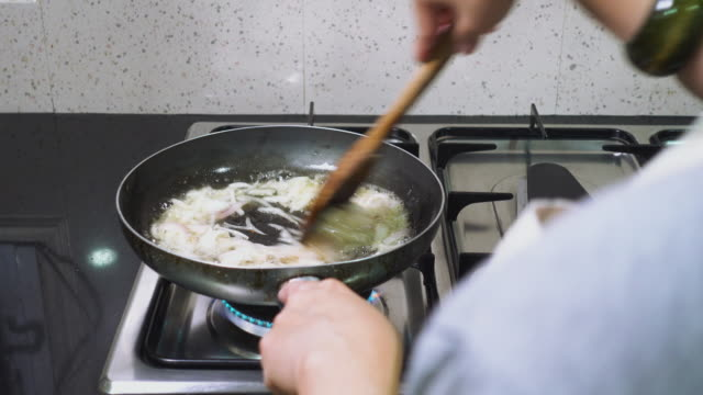 close up shoulder view of woman use turner frying onion slice with oil in pan on gas stove in kitchen at home.cooking food. - cooker stock videos and b-roll footage
