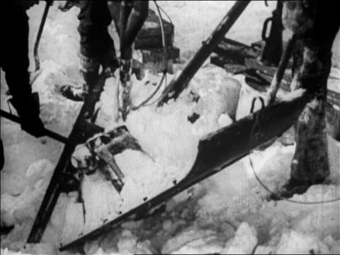 b/w 1926 close up shovels digging snow from skis on byrd's airplane before flight over north pole / news - 1926 stock videos & royalty-free footage