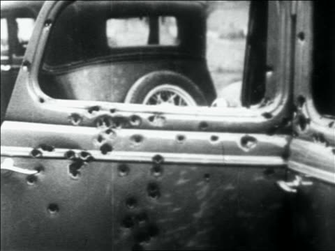 stockvideo's en b-roll-footage met close up side of car full of bullet holes + with broken windows / bonnie + clyde's car - 1934